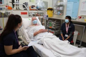 Emergency Department Dr Fiona Liew (left) and Dr (HMO) Karunya Yogheswaran (right) chat with patient John Jolley at West Gipps Hospital